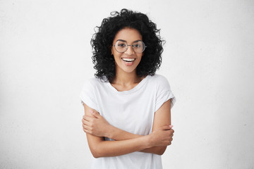 Pretty woman in white t-shirt and round eyeglasses feeling shy and a bit uncomfortable, smiling nervously in closed posture, keeping arms crossed while talking to handsome male who she likes