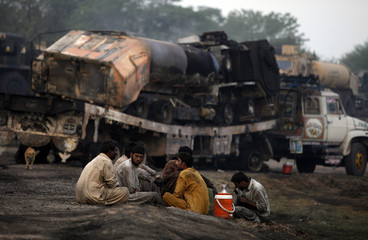 Men sit near damaged trucks after they were attacked and burnt in a field in Sangjani, located in the outskirts of Islamabad