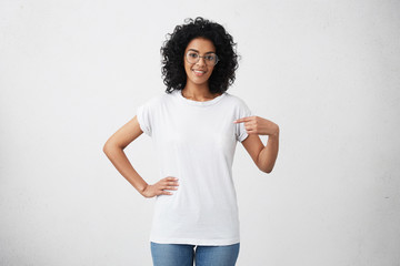 Clothing, design and advertising concept. Indoor shot of positive friendly young mixed race female in glasses pointing at copy space on her blank white t-shirt for your text or promotional content