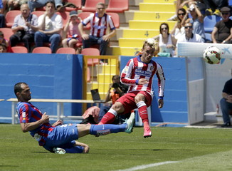 Atletico Madrid's Griezmann falls next to Levante's Vyntra during their Spanish first division soccer match at the Ciudad de Valencia stadium in Valencia