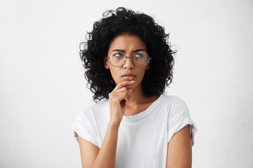 Hmm. Suspicious thoughtful young mixed race female with black curly hair looking up, keeping hand on her face as if trying hard to remember something important. Human face expressions and emotions