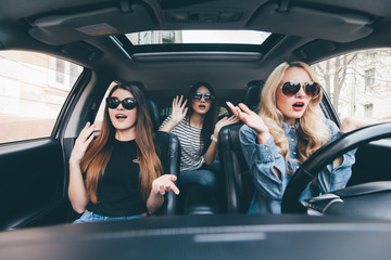 Beautiful stylish girls are sitting with open mouth while having shock during the car driving