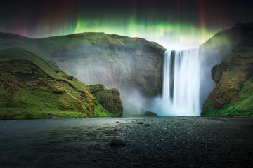 Photo sur Toile Aurore polaire Green aurora light behind famous Skogafoss waterfall