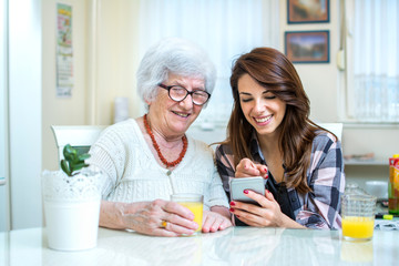 Adult granddaughter showing something on mobile phone to her senior grandmother at home.