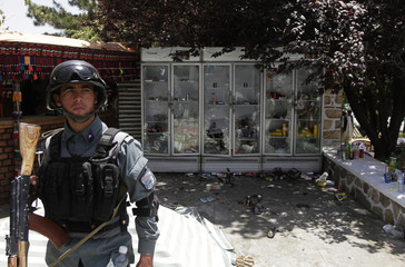 An Afghan policeman keeps watch at the site of an attack at a hotel on the outskirts of Kabul