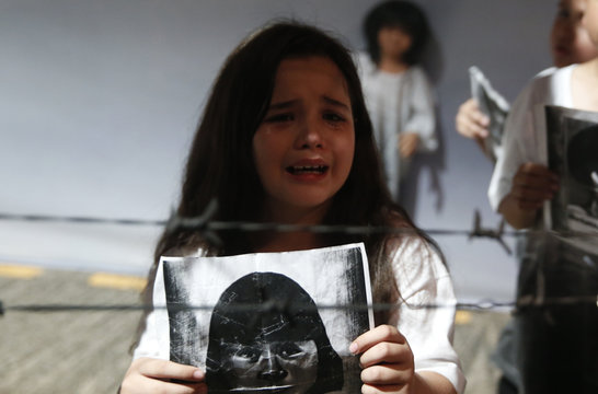 A girl portraying a daughter of a martial law victim holds a picture as she cries inside a People Power Experiential Museum at a military Camp Aguinaldo in Quezon City, Metro Manila