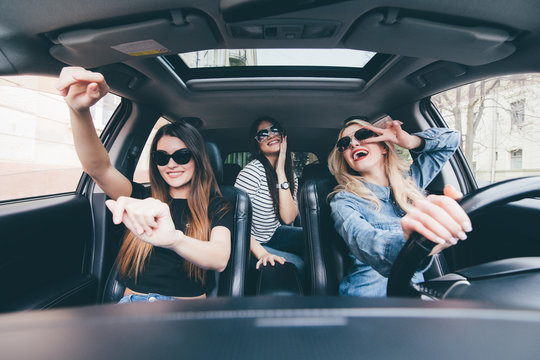three girls driving in a convertible car and having fun, listen music and dance