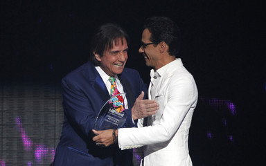 "Singer Anthony presents an ""Artistic Career"" award to singer Carlos at the 2015 Latin Billboard Awards in Coral Gables"