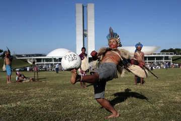 An indigenous Indian kicks a soccer ball during a protest in Brasilia