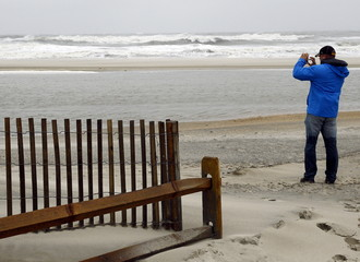 A visit to the beach takes photographs of the storm surf with his cellphone camera as a nor-easter comes on shore in Ocean City