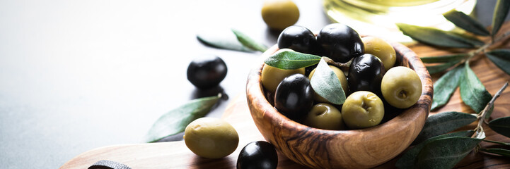 Black and green olives in wooden bowl Wall mural