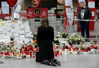 Woman kneels in front of candles and flowers as she prays for the victims of Germanwings Flight 4U9525 at Duesseldorf airport