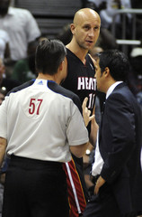 Heat center Ilgauskas is restrained by referee Willard and coach Spoelstra after throwing the basketball at Hawks Pachulia in the second half of their NBA basketball game in Atlanta