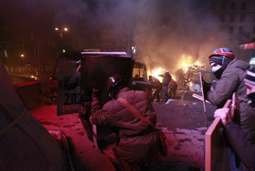 Pro-European integration protesters take cover behind shields among burnt out vehicles during clashes with Ukrainian riot police in Kiev