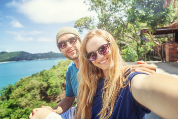 Young happy couple doing selfie on mobile phone overlooking beautiful tropical landscape