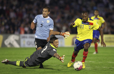 Ecuador's Benitez challenges Uruguay's goalkeeper Muslera and Gargano during their 2014 World Cup qualifying soccer match in Montevideo