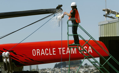 Oracle Chief Marketing Officer Sim breaks a bottle of champagne on the bow sprit of the latest Oracle Team USA AC72 catamaran in San Francisco