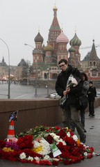 People come to lay flowers at the site, where Boris Nemtsov was shot dead, with St. Basil's Cathedral seen in the background, in central Moscow