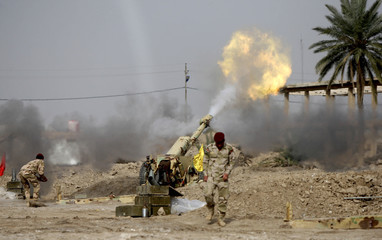Personnel from Iraqi security forces fire a cannon during clashes with the al Qaeda-linked Islamic State in Iraq and the Levant (ISIL) in Jurf al-Sakhar