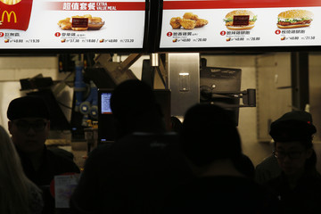 "Customers line up as ""Temporary Unavailable"" stickers are placed on pictures of chicken nuggets and chicken filet on the menu at a McDonald's restaurant in Hong Kong"