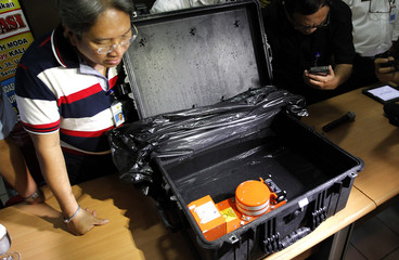 Indonesian official looks at the cockpit voice recorder of AirAsia QZ8501 during news conference at the National Transportation Safety Committee office in Jakarta