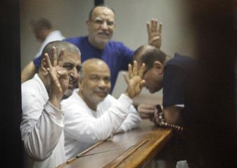 Senior Muslim brotherhood leaders wave with the Rabaa sign as they sit behind bars during their trial on charges of spying and terrorism at a court in the police academy on the outskirts of Cairo
