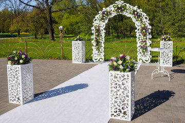 White lace wedding arch and chairs for guests. Vases with purple flowers. The wedding ceremony area at the wedding