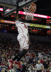 University of Louisville's Russ Smith dunks the basketball over top the University of Memphis defense during the first half of play in their NCAA basketball game at the KFC Yum! Center in Louisville