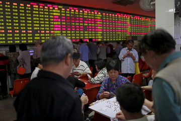 Investors play cards in front of a screen showing stock information at a brokerage house in Shanghai