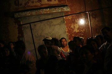 A street vendor watches as a Holy Week procession passes by in Guatemala City