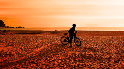 Man with bicycle on the beach
