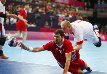 Croatia's Jakov Gojun takes a shot challenged by Denmark's Rene Toft Hansen in their men's handball Preliminaries Group B match at the Copper Box venue during the London 2012 Olympic Games