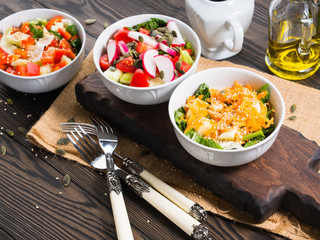 Colorful vegetable salad bowl for lunch on wooden rustic background