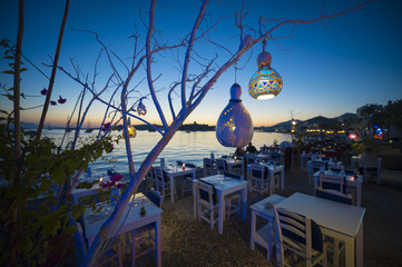 Informal beachside seating with decorative gourd lights hanging from a tree in Bodrum, Turkey