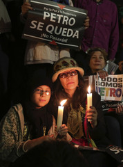 Demonstrators hold candles and signs during a protest in support of Bogota Mayor Petro in Bolivar Square