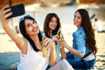 Three young women having fun on the beach drinking beer and doing selfie Fototapete
