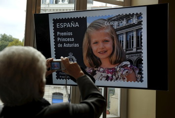 A woman photographs a tv screen displaying a picture of Leonor, Princess of Asturias, during the presentation of a series of postage stamps at the Campoamor theatre in Oviedo