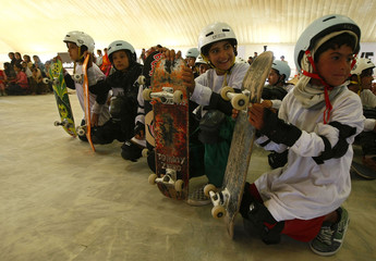 Afghan children hold their skateboards as they wait in line to take part in a skateboarding competition in Kabul