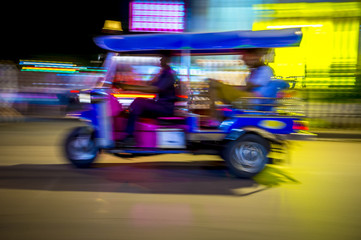 A tuk-tuk taxi zooms by in a brightly colored lights night blur in Bangkok,  Thailand