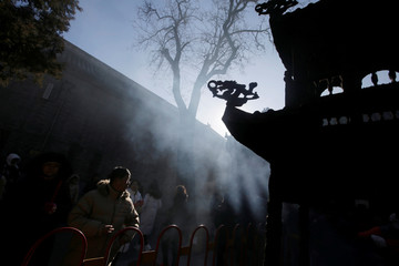 People walk amidst  the smoke while burning incense to pray for good fortune on the fifth day of the Chinese Lunar New Year in Beijing
