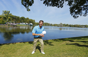 Phelps stops to have his picture taken by spectators on the second fairway during the Captains and Celebrity Scramble at the 39th Ryder Cup golf matches at the Medinah Country Club