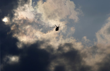 A Canadian Armed Forces Griffon helicopter flies toward stormy skies during the 100th anniversary of the Calgary Stampede Rodeo in Calgary