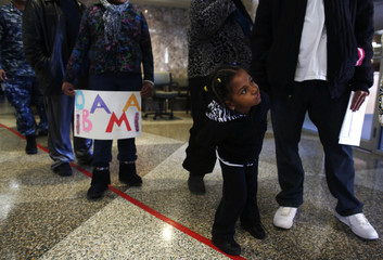 A girl checks out the line as she queues with her father and other residents to cast their early votes in the upcoming U.S. presidential elections in Milwaukee
