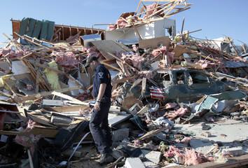 Wallbridge Police officer Matt Simon looks through the debris of the destroyed Lake Township police headquarters in Lake Township, Ohio