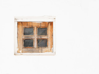 Small wooden window on a white wall, a rustic authentic house, a rural background. Old traditional Ukrainian house, wattle and daub hut. Background with space for text