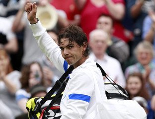 Rafael Nadal of Spain waves after defeating Ryan Sweeting of the U.S. at the Wimbledon tennis championships in London