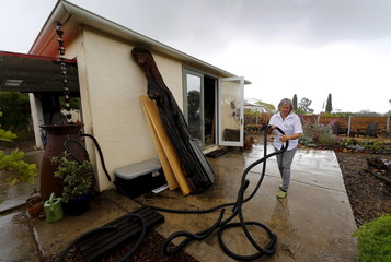 Woman places her overflow watering line into her garden to harvest the water in San Diego