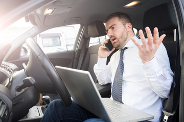 Stressed businessman working seated in car