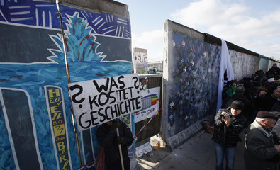"""A man holds a banner during a protest at the open air 0.8-mile painted section of the Berlin Wall known as the """"East Side Gallery"""" in Berlin"""