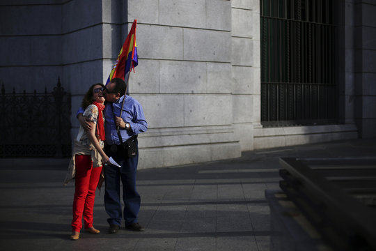 A man kisses a woman as he holds Spanish Republican flag during rally to mark 83rd anniversary of Spain's Second Republic in Madrid